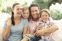 放松在沙发的年轻家庭画象 库存图片