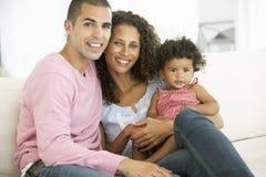 放松在沙发的年轻家庭 图库摄影