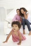 放松在沙发的年轻家庭 库存图片