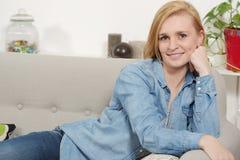 放松在沙发的年轻白肤金发的妇女 免版税图库摄影