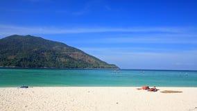 放松在沙子海滩的夫妇可及棕褐色酸值Lipe 免版税库存照片