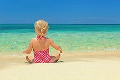 放松在沙子海滩边缘的小女孩 免版税库存照片