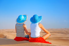 放松在沙漠的帽子的两个女孩 免版税库存照片