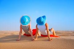 放松在沙漠的帽子的两个女孩 库存图片