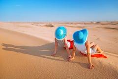 放松在沙漠的帽子的两个女孩 免版税库存图片