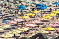 放松在沙滩伞下的人们 免版税图库摄影