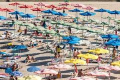 放松在沙滩伞下的人们 免版税库存图片