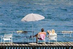 放松在河码头的年轻夫妇 库存照片