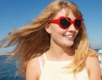 放松在沿海的红色太阳镜的女孩 免版税库存照片
