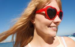 放松在沿海的红色太阳镜的女孩 图库摄影