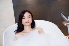 放松在泡沫似的浴的妇女 库存图片