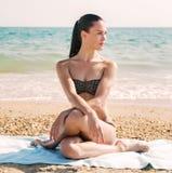 放松在波浪的一个海滩的一名美丽的妇女的照片 免版税库存图片