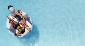放松在浮动水池可膨胀的玩具的女孩 免版税库存图片