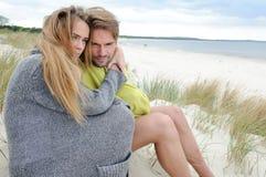 放松在海岸-沙丘的有风秋天天,海滩,美好的夫妇 库存图片