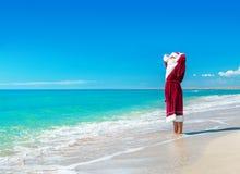 放松在海海滩-圣诞节概念的圣诞老人 免版税库存照片