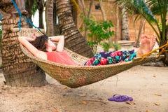 放松在海滩的一个吊床的少妇在暑假期间 免版税图库摄影
