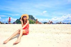 放松在海滩的一件桃红色礼服的亚裔妇女 库存照片