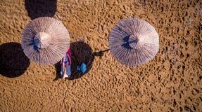 放松在海滩的一把伞下的一名孤立妇女的空中射击 免版税库存照片