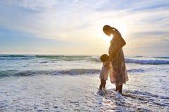 放松在海滩的剪影女儿拥抱的怀孕的母亲在日落 免版税库存图片
