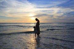 放松在海滩的剪影怀孕的母亲和女儿在日落 免版税库存照片