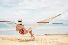 放松在海滩的吊床夏天休假的亚裔妇女 图库摄影