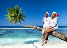 放松在海滩的夫妇在圣诞节期间 免版税库存照片