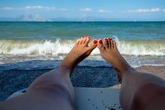 放松在海滩的少妇在观看波浪的希腊通过她的腿和红被绘的钉子 免版税库存图片