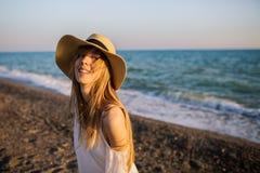 放松在海滩的年轻愉快的女孩 免版税图库摄影
