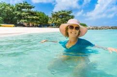 放松在海滩的年轻美丽的妇女 免版税库存照片