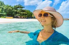 放松在海滩的年轻美丽的妇女 免版税库存图片