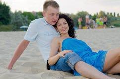 放松在海滩的新夫妇 图库摄影