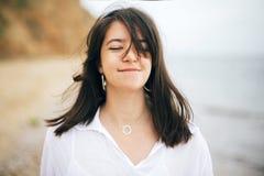 放松在海滩的时髦的行家女孩 ?? 享受时间和微笑在有风海的愉快的boho妇女画象  免版税库存图片