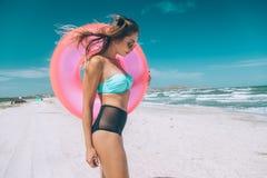 放松在海滩的桃红色lilo的女孩 库存图片