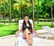 放松在海滩睡椅的年轻美丽的妇女由水池 热带假期在加勒比 免版税库存照片