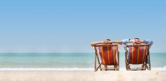 放松在海背景的椅子海滩的夫妇 免版税库存图片