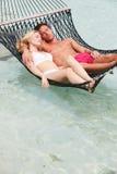 放松在海滩吊床的夫妇 免版税库存照片