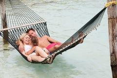 放松在海滩吊床的家庭 免版税库存图片
