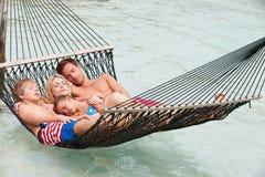 放松在海滩吊床的家庭 库存照片