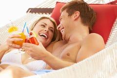 放松在海滩吊床的浪漫夫妇 免版税库存照片