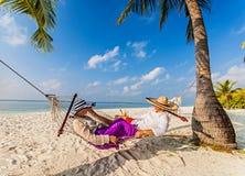 放松在海滩吊床的浪漫夫妇 图库摄影