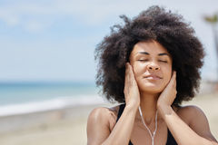 放松在海滩听的音乐的美国黑人的妇女 免版税库存照片