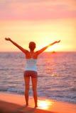 放松在海滩日落的愉快的自由妇女 免版税图库摄影