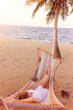 放松在海滩的一个吊床的妇女 免版税库存照片