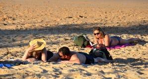 放松在海滩的人们 妇女在背景中的读一本书 夫妇谈话在f 库存照片