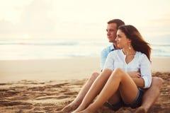 放松在海滩的夫妇观看日落 免版税库存照片
