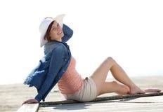 放松在海滩的快乐的少妇 免版税图库摄影