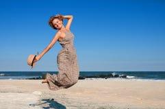 放松在海滩的愉快的妇女旅客 免版税库存图片