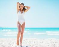 放松在海滩的愉快的少妇全长画象  免版税库存图片