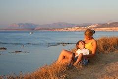 放松在海滩的日落的母亲和儿子 免版税库存照片