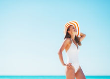 放松在海滩的泳装和海滩帽子的愉快的少妇 免版税库存照片